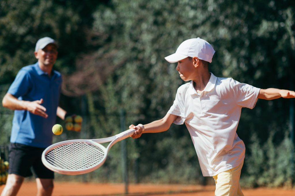 Tennis Instructor with Boy in Tennis Lesson.